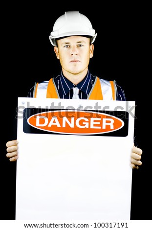Man with construction helmet holding blank 'danger' sign on black background - stock photo