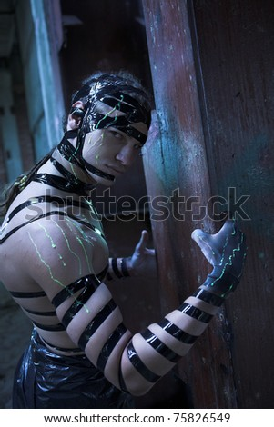 Man with creative face-art. Cyber zombi style. Shot in destroyed building. - stock photo