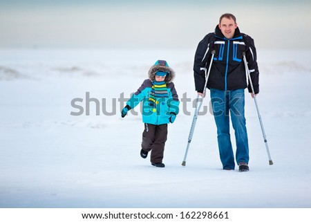 Man with crutches together with son walking along winter beach - stock photo
