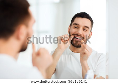 man with dental floss cleaning teeth at bathroom - stock photo