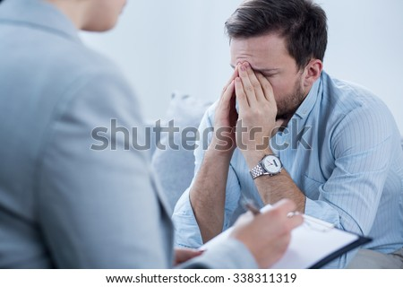 Man with depression crying during psychotherapy session - stock photo