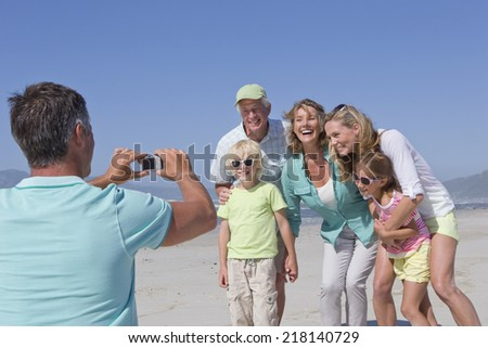 Man with digital camera photographing multi-generation family on sunny beach - stock photo