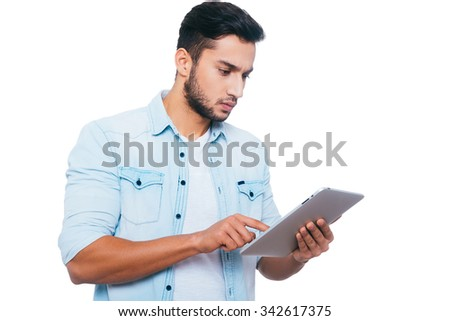 Man with digital tablet. Handsome young Indian man working on digital tablet while standing against white background - stock photo