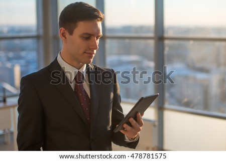 Man with digital tablet standing in modern office interior.