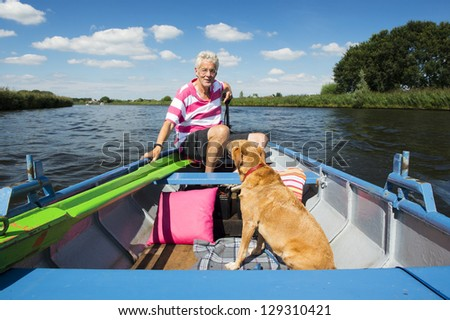 Man with dog in boat at the river - stock photo