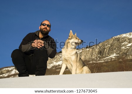 Man with dog in winter forest - stock photo