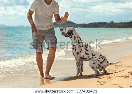 man with dog on the tropical beach  - stock photo