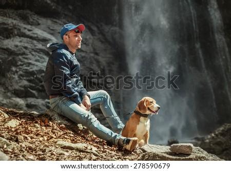 Man with dog sitting near waterfall - stock photo