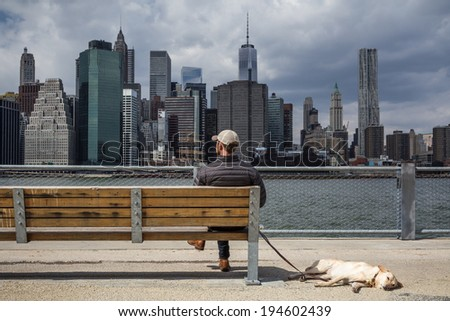 Man with dog sitting on a bench an enjoys the view of the Manhattan skyline, New York City - stock photo