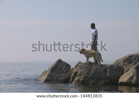 Man with dog standing on rocks at beach