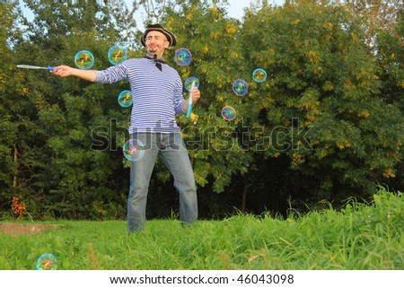 man with drawed beard and whiskers in pirate suit is blowing soap bubbles. - stock photo