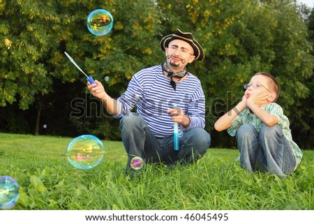 man with drawed beard and whiskers is looking at one soap bubble. his son is looking to one soap bubble too and blow on it. - stock photo