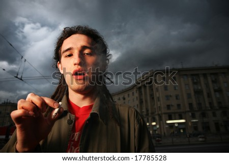 Man with dreadlocks smoking on street