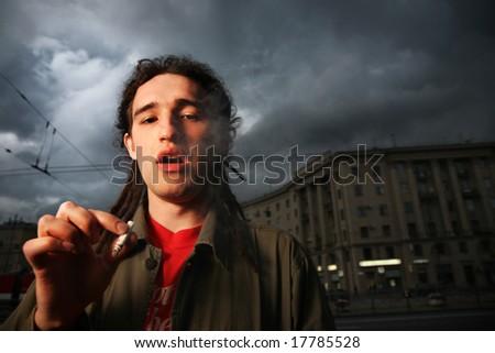 Man with dreadlocks smoking on street - stock photo