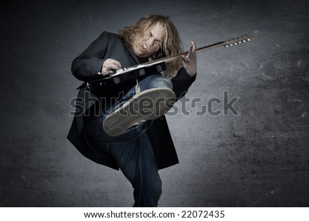 Man with electric guitar jumping and playing rock music - stock photo