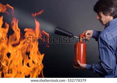 man with extinguisher fighting a fire - stock photo