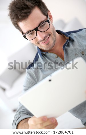 Man with eyeglasses websurfing with touchpad - stock photo
