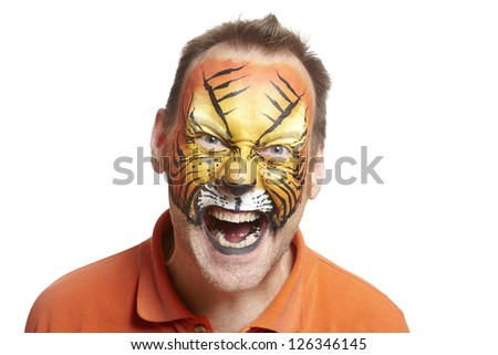 Man with face painting tiger smiling on white background - stock photo