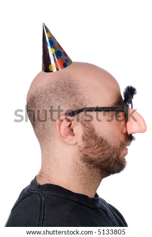 Man with fake nose and  party hat with mustashe and eyebrows over awhite background - stock photo