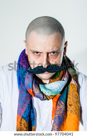 Man with false moustache wearing colored scarf around his neck - stock photo