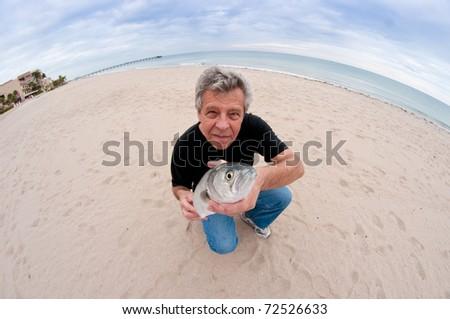 Man with fish - through a fish-eye lens - stock photo