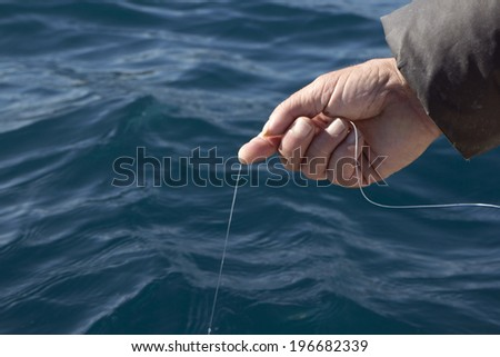 Man with fishing line in his hand catching fish from the side of the boat - stock photo