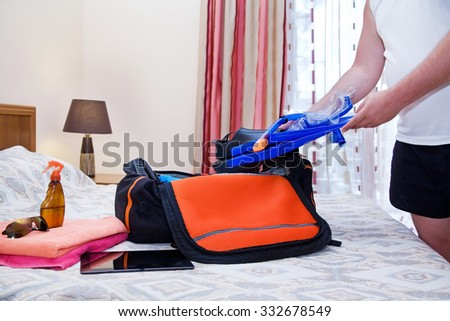 Man with flippers and travel bag going to the resort - stock photo