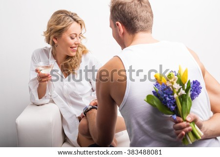 Man with flowers behind his back surprising woman  - stock photo