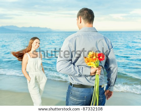 Man with flowers for his woman. Focus on a flowers