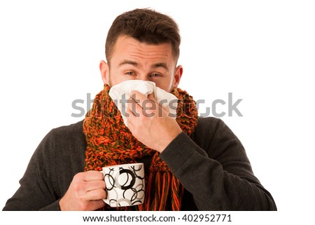 Man with flu and fever wrapped in scarf holding cup of healing tea and handkerchief isolated over white. - stock photo
