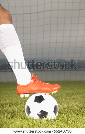 Man with foot on soccer ball - stock photo