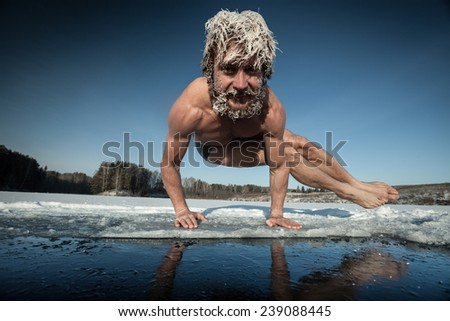 Man with frozen hair doing yoga exercise (parsva bakasana) on the ice - stock photo