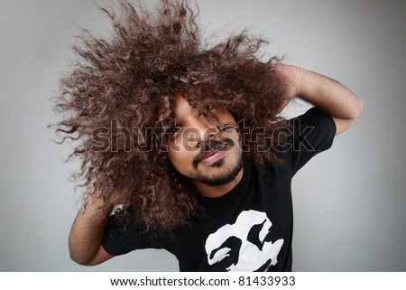 Man with funky hairstyle gives an unusual pose - stock photo