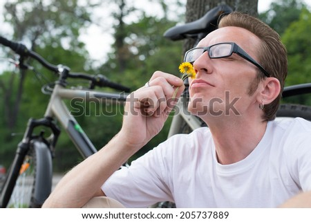 man with funny face sniffing the flower