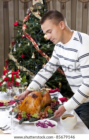 Man with Garnished Thanksgiving roasted turkey to celebrate traditional family dinner with salad, fruits, vegetables, wine and champagne glasses on Christmas tree background - stock photo