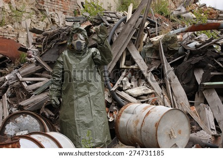 Man with gas mask and green military clothes  explores  after chemical disaster. - stock photo