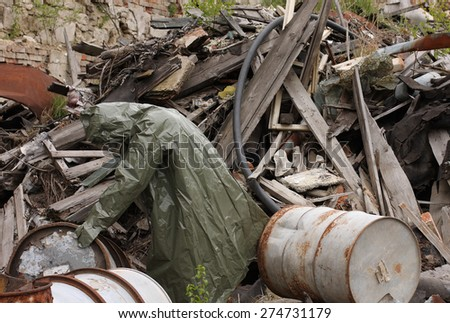 Man with gas mask and green military clothes  explores barrels  after chemical disaster. - stock photo