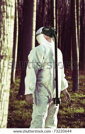 Man with gas mask in the forest - stock photo