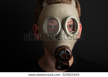 Man with gas mask on black  background. - stock photo