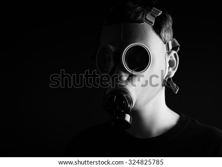 Man with gas mask on black  background.Black and white photo. - stock photo