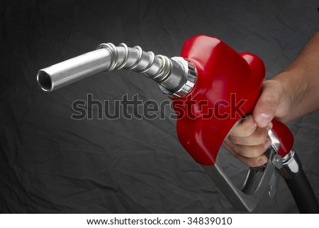 Man with gas nozzle in hand at gas station - stock photo