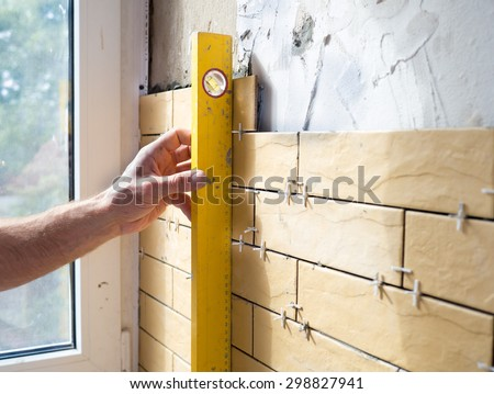 Man with gauge measuring  vertical linearity of installation ceramic tiles during renovation - stock photo