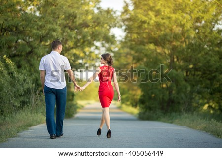 Man with girl on nature holding hands and walking away by the road. Relationships - stock photo
