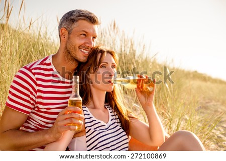 man with girl summerending relaxing watching sun - stock photo