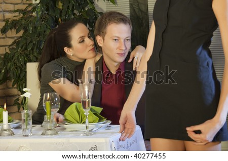 man with girlfriend looking at another woman in restaurant - stock photo