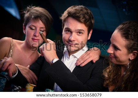 Man with glamorous women in casino at poker table - stock photo
