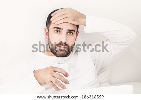 Man with glass of water lying on the bed holding his head. Headache. - stock photo