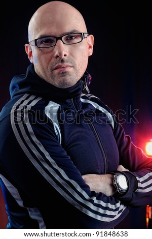 Man with glasses and in a sports suit. Studio-style portrait