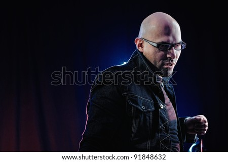 Man with glasses and in denim jacket. Studio-style portrait