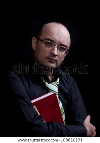 Man with glasses holding red book. Isolated over black.